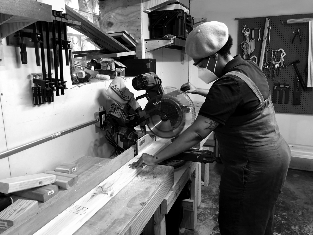 image of a person cutting a piece of wood in a woodshop.
